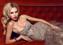 Gorgeous woman with blond hair in elegant dress lying on red div Stock Photography