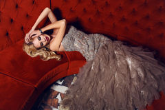 Gorgeous woman with blond hair in elegant dress lying on red divan. Fashion interior photo of gorgeous woman with blond hair in elegant dress lying on red divan Stock Image