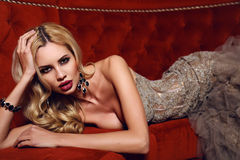 Gorgeous woman with blond hair in elegant dress lying on red divan Royalty Free Stock Photography