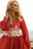 Gorgeous woman with blond hair in elegant dress posing on beach Stock Photography