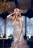 Gorgeous woman with blond hair in elegant dress posing in luxury Royalty Free Stock Images