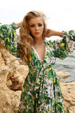 Gorgeous woman with blond hair in elegant summer dress posing on beach Royalty Free Stock Photos