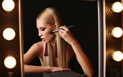 Gorgeous  woman with blond hair and evening makeup. Fashion studio photo of gorgeous sensual woman with blond straight hair and evening makeup posing in dressing Royalty Free Stock Images