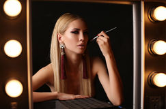 Gorgeous  woman with blond hair and evening makeup. Fashion studio photo of gorgeous sensual woman with blond straight hair and evening makeup, sitting in Royalty Free Stock Images
