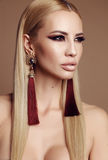 Gorgeous  woman with blond hair and extravagant makeup. Fashion studio photo of gorgeous sensual woman with blond straight hair and extravagant makeup Royalty Free Stock Image