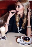 Gorgeous woman with blond hair sitting in cafe with coffee and dessert Royalty Free Stock Photo