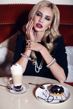 Gorgeous woman with blond hair sitting in cafe with coffee and dessert Stock Image