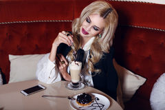 Gorgeous woman with blond hair sitting in cafe with coffee and dessert Stock Photography