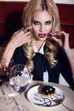 Gorgeous woman with blond hair sitting in cafe with wine and dessert Royalty Free Stock Image