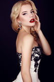Gorgeous woman with blond hair wears luxurious party dress and bijou Royalty Free Stock Photos