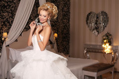 Gorgeous woman with blond hair wears luxurious wedding dress and bijou Stock Image