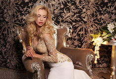 Gorgeous woman with blond hair wears luxurious wedding dress and bijou Royalty Free Stock Photos