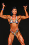 Gorgeous Woman Bodybuilder Flexes Double Biceps. Beautiful, athletic bodybuilder Kayla Booker strikes a double biceps pose as she earns 7th place in the Open B Royalty Free Stock Images