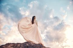 Gorgeous woman brunette in the mountains at sunset and blue sky with clouds. The woman looks into the distance in a long white. Dress developing in the wind royalty free stock photos