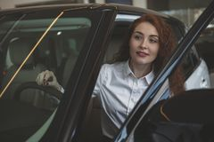Gorgeous woman buying new car at the dealership stock image