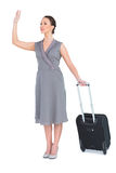 Gorgeous woman carrying her suitcase calling taxi Royalty Free Stock Image