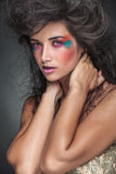 Gorgeous woman with colorful make up looking at the camera. While holding both hands to her neck Stock Photos