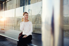 Gorgeous woman with cute smile having pleasant conversation on smart phone while she waiting public transport on bus stop, Royalty Free Stock Image