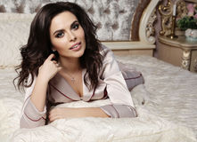 Gorgeous woman with dark hair in cozy pajamas lying in bed Royalty Free Stock Photo