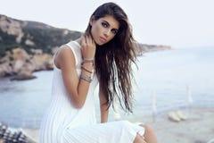 Gorgeous woman with dark hair in elegant dress on beach stock image