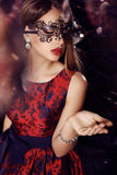 Gorgeous woman with dark hair  in elegant dress and mask Stock Photography