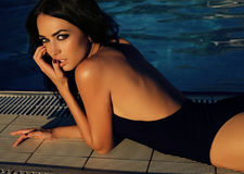 Gorgeous woman with dark hair in elegant swimsuit. Fashion outdoor photo of gorgeous woman with dark hair in elegant swimsuit posing beside swimming pool Royalty Free Stock Images