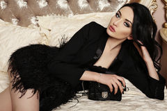Gorgeous woman with dark hair and evening makeup. Fashion interior photo of gorgeous woman with dark hair and evening makeup, in elegant clothes with bag Stock Photo