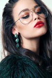 Gorgeous woman with dark hair in luxurious fur coat. Fashion studio photo of gorgeous woman with dark hair in luxurious fur coat and glasses royalty free stock images