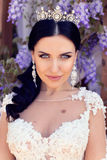 Gorgeous woman with dark hair in luxurious wedding dress. Fashion summer outdoor photo of gorgeous bride with dark hair in luxurious wedding dress posing at stock photos