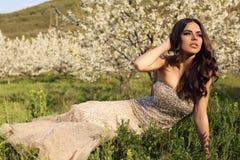 Gorgeous  woman with dark hair posing in spring garden Stock Photo