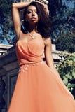 Gorgeous woman with dark hair wears luxurious dress and bijou Stock Photo