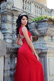 Gorgeous woman with dark hair wears luxurious dress and bijou Stock Images