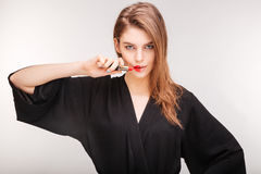 Gorgeous woman demonstrating red lipstick on half of her lips Stock Images
