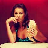 Gorgeous woman eating kebab in night club stock photography