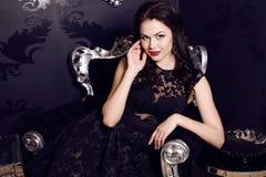 Gorgeous woman in elegant black  dress posing in luxurious interior Royalty Free Stock Photo