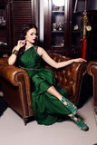 Gorgeous woman in elegant green dress posing in luxurious interior Stock Images