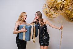 Gorgeous woman with elegant hairstyle holding big gift with surprised face expression. Indoor photo of two pretty girls. Gorgeous women with elegant hairstyle royalty free stock image