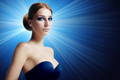 Gorgeous woman with evening makeup on a blue background Royalty Free Stock Image
