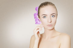 Gorgeous woman face with orchid flower over beige background Stock Photography