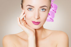 Gorgeous woman face with orchid flower over beige background Royalty Free Stock Photos