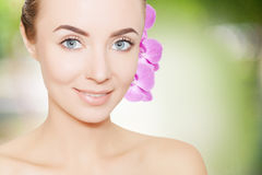 Gorgeous woman face with orchid flower over green background Stock Images