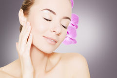 Gorgeous woman face with orchid flower over grey background Royalty Free Stock Photo