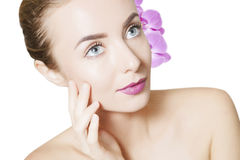 Gorgeous woman face with orchid flower over white background Stock Images