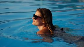 Gorgeous woman is going for a swim. Young woman is taking sunbath in the pool and then go for a swim. Hiding her eyes behind sunglasses stock video