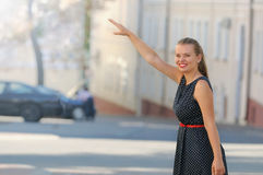 A gorgeous woman hailing a cab after a long day of clothes shopp Royalty Free Stock Photography