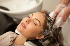 Gorgeous woman having her hair washed by hairdresser. Close up of a beautiful young women enjoying head massage with her eyes closed, while professional royalty free stock images
