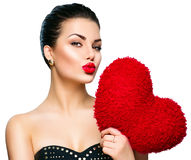 Gorgeous woman with heart shaped red pillow Royalty Free Stock Photography