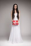 Gorgeous woman holding gift. Young beautiful woman with long dark hair wearing maxi white dress, holding gift wrapped in red paper with  white ribbon Stock Photography