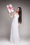 Gorgeous woman holding gift. Young beautiful woman with long dark hair wearing maxi white dress, holding gift wrapped in white paper with red ribbon Stock Photos