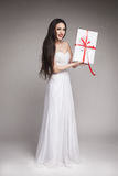 Gorgeous woman holding gift. Young beautiful woman with long dark hair wearing maxi white dress, holding gift wrapped in white paper with red ribbon Stock Photo